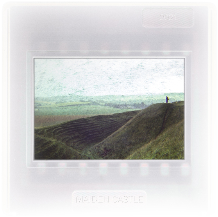 A solitary figure stands on the rampants of Maiden Castle, an Iron Age hillfort
